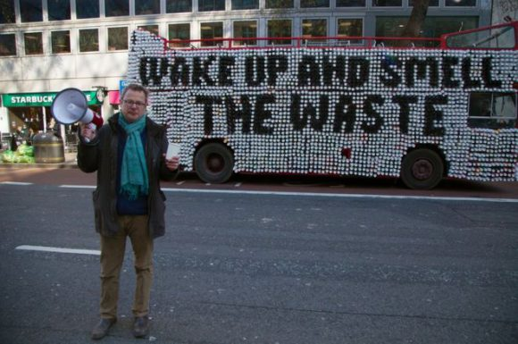 A man with a foghorn and a cup standing in front of a double decker bus with coffee cups on its side that spell out 'Wake up and smell the waste.'