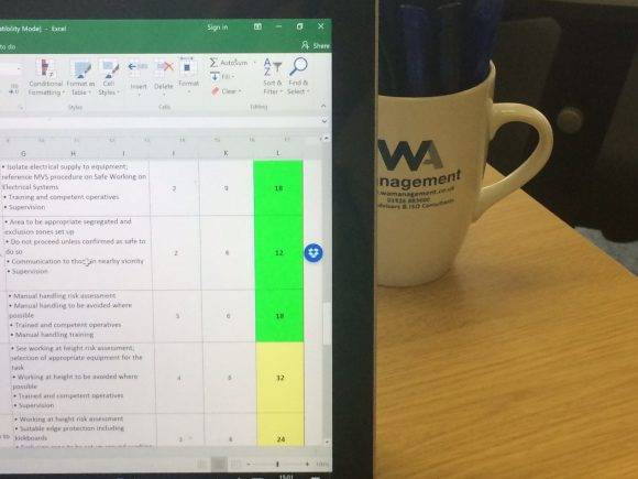 A computer screen and a WA Management mug with pens in on a desk.