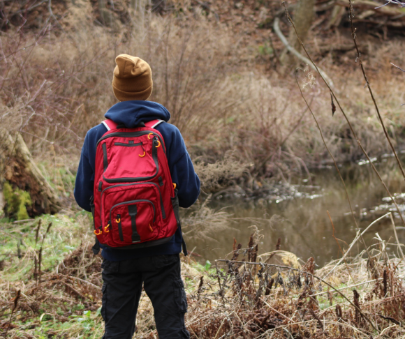 A person wearing a red backpack in the outdoors.