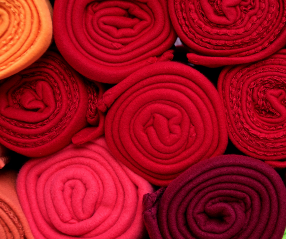 Rolled-up pieces of fabric in different shades of red.