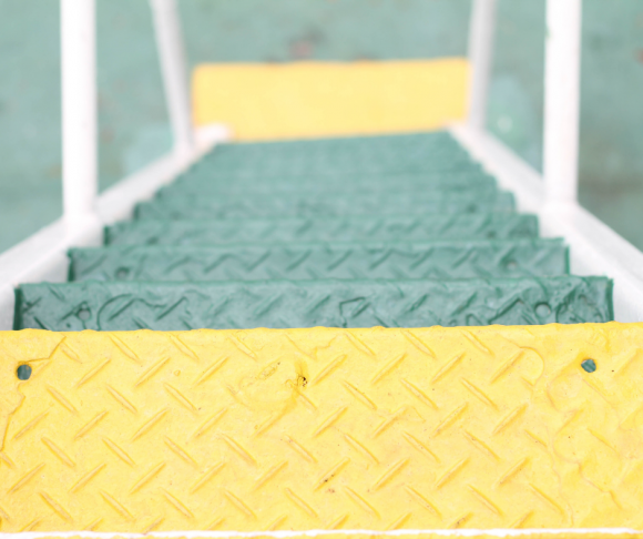 A ladder with green and yellow rungs.