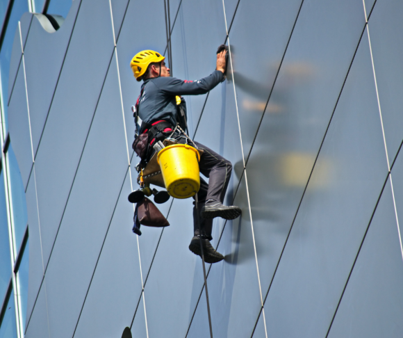 A person working at height against the side of a building with a harness on.