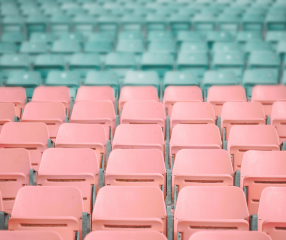 Rows of pink and blue chairs in a stadium.