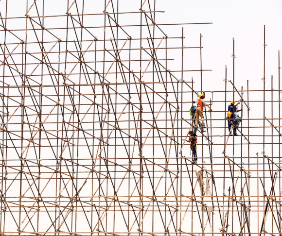 Construction workers working at height on scaffolds.