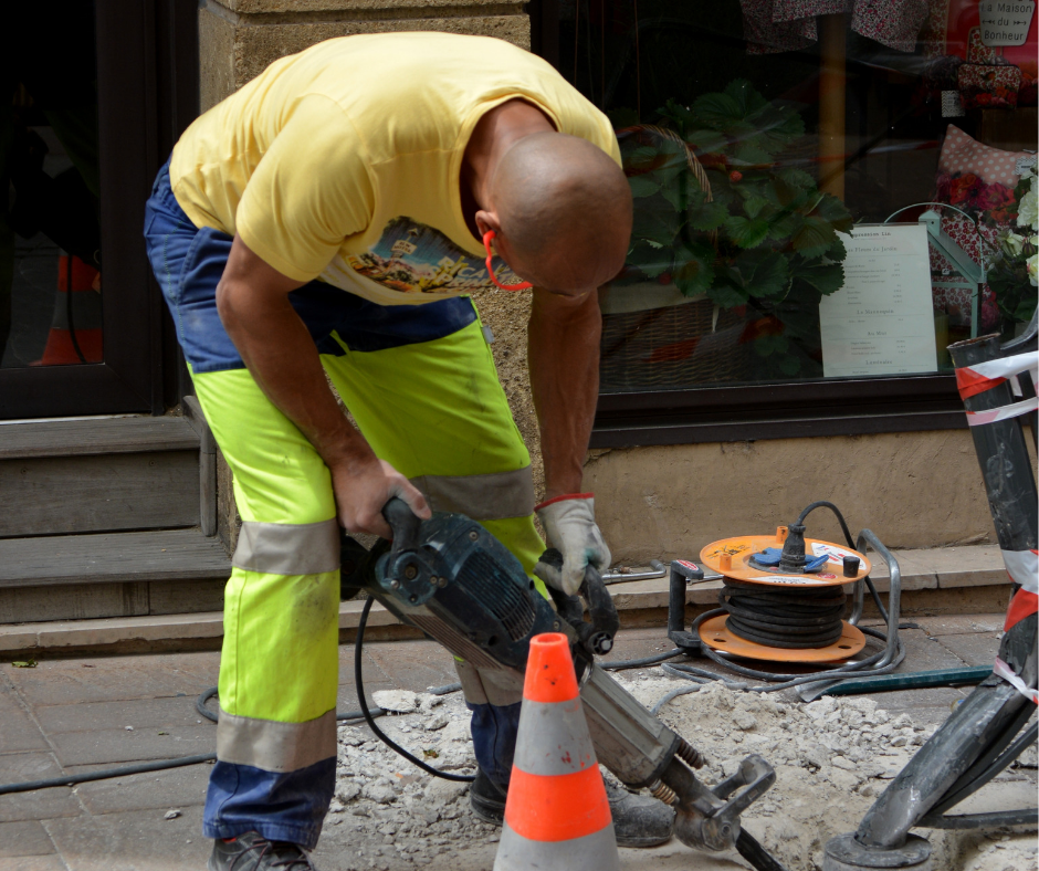 A man drilling in hi-vis trousers and a yellow top, with earplugs in.