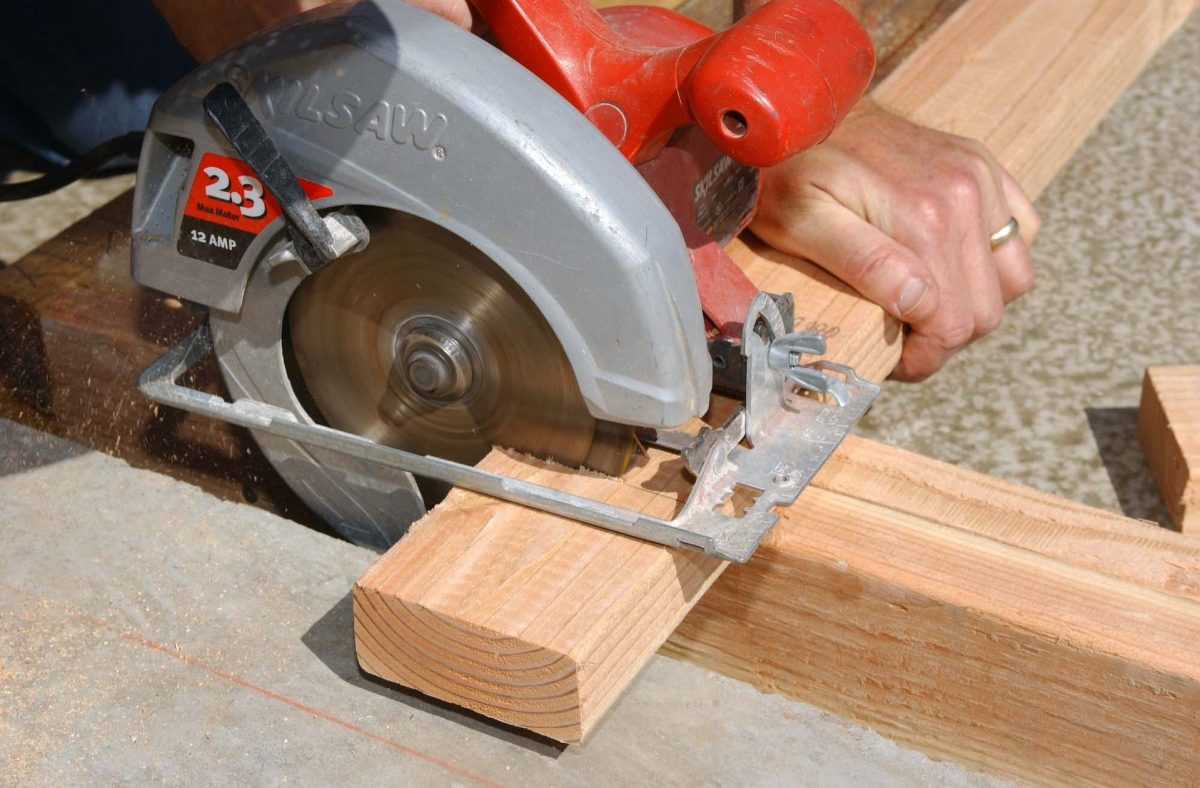 Cutting wood with a saw.