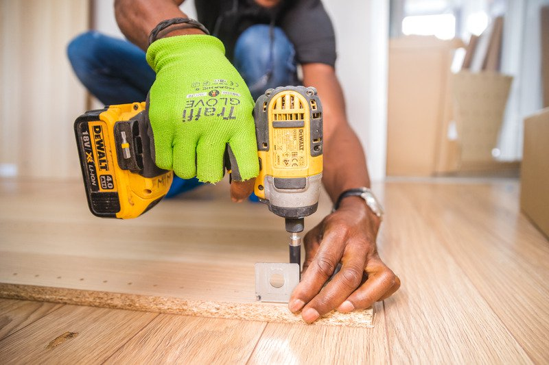 A person drilling with a yellow and black drill, wearing a pair of bright green safety gloves.