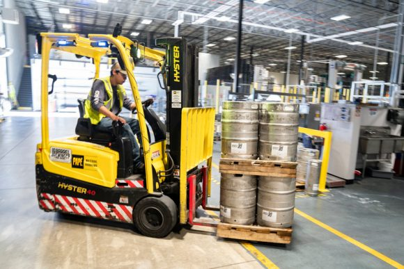 A worker driving a forklift with silver canisters on.