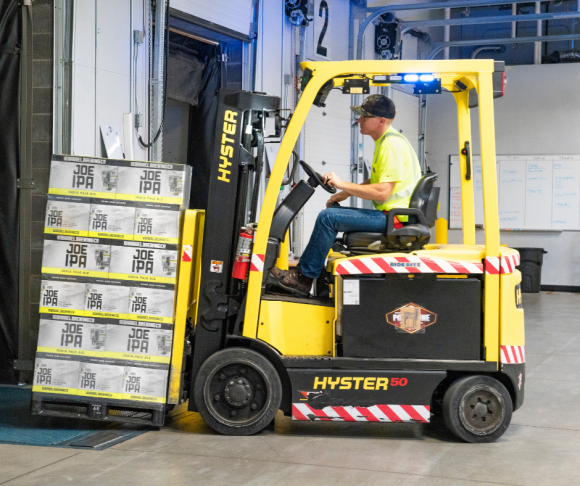 A worker driving a forklift with products on.