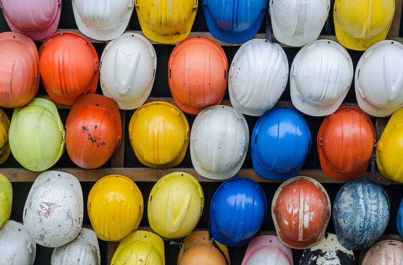A collection of different coloured hard hats.