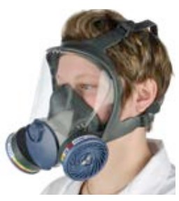 A person wearing a full face mask breathing apparatus with a gas / vapour filter .