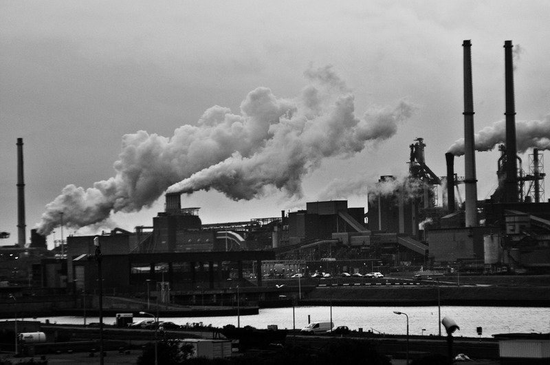 A factory with smoke billowing out it's towers, in black and white.