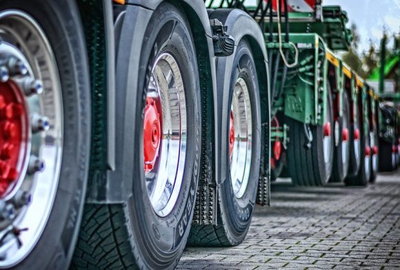 Wheels of a truck with a red centre, with another green truck behind them.