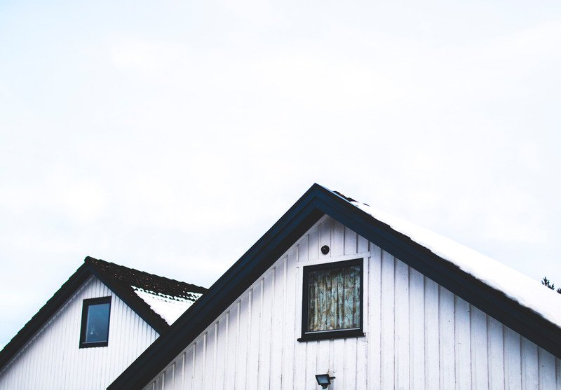 Two white paneled roofs with a black trim and windows below it.