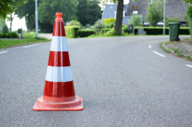 A red and white striped cone on a road.