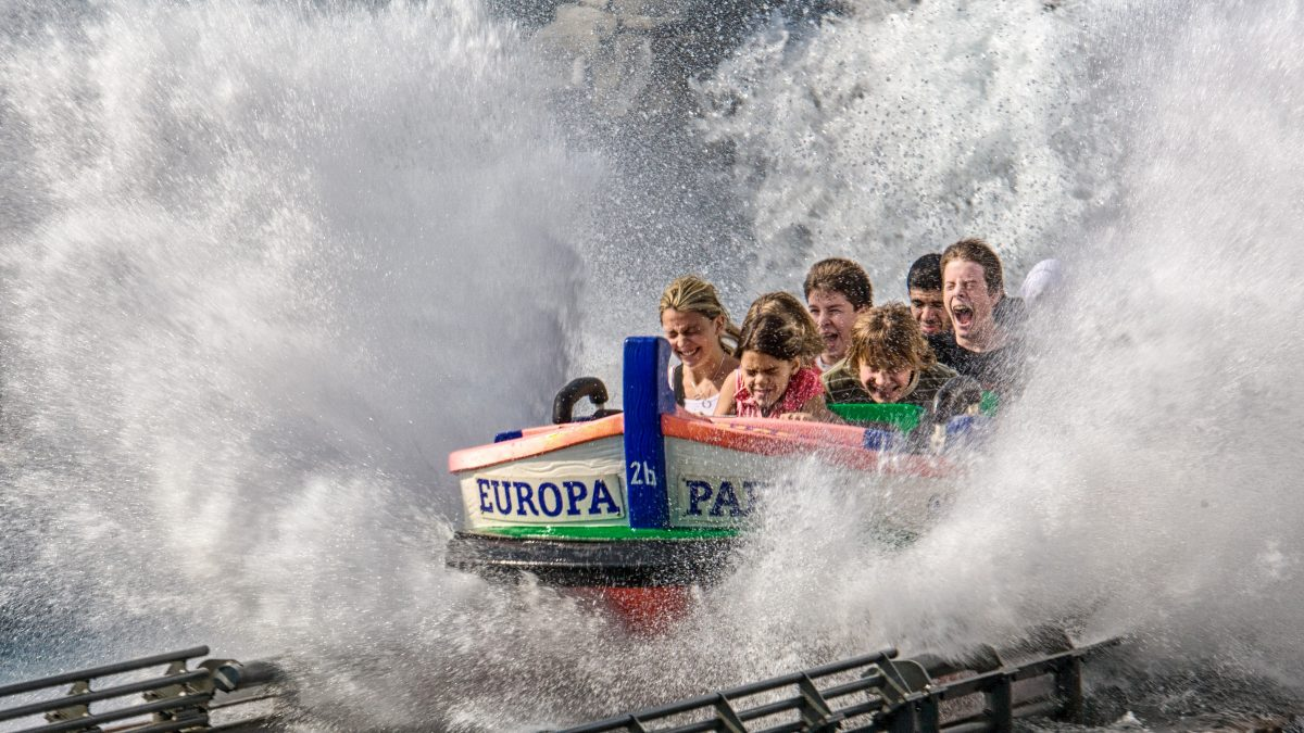 People on a water park ride where a boat is speeding through water, splashing them.