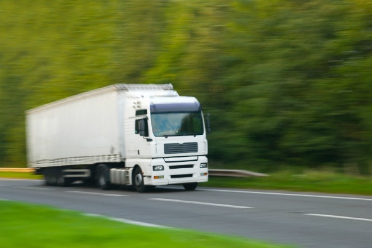 A white HGV driving on a road past trees, slightly blurred to indicate its speed.