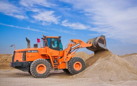 An orange and black excavator picking up sand against a blue sky with some clouds in it.