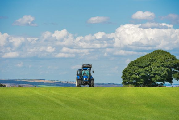 A blue tractor on a green field with a tree against a cloudy blue sky.