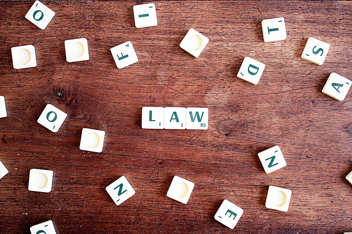 Scrabble tiles spread across a wooden surface, with three put together to create the word 'Law'