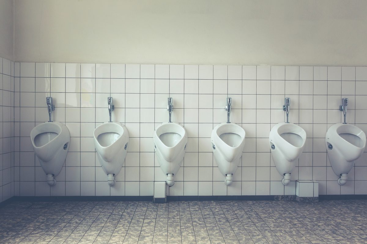 A line of urinals against a white tiled wall in a public bathroom.