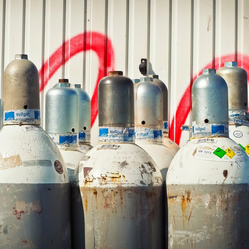 A collection of rusted gas cylinders against a white ridged wall with red spray paint on.