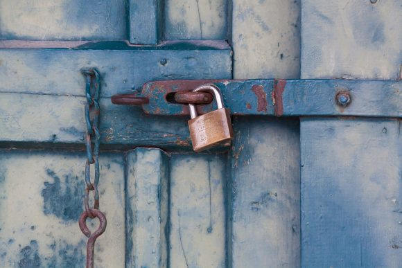 A rusted door locked with a padlock.