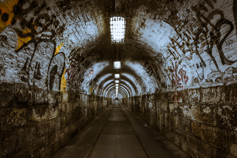 An underground tunnel that has graffiti along the walls.