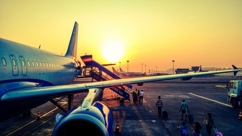One side of an airplane with people queuing to get it on it, with a sunset in the background.