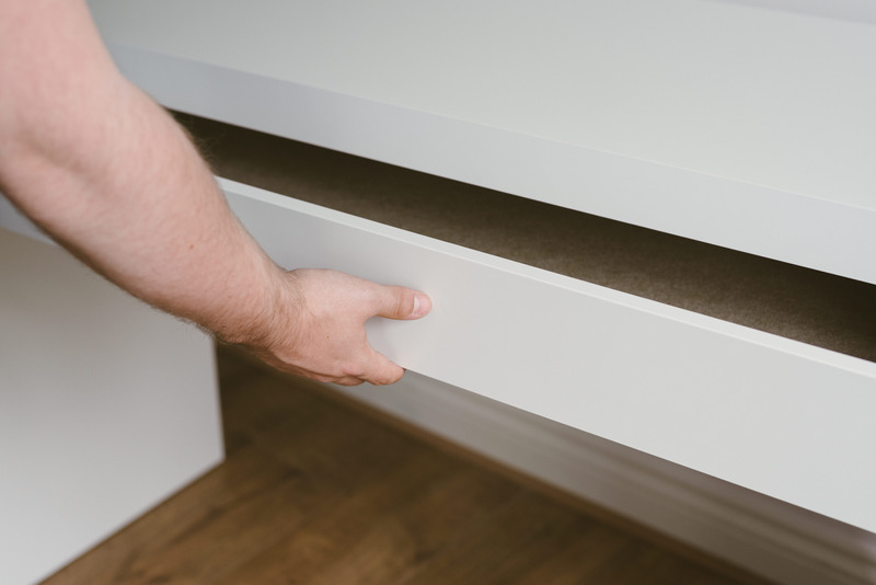 A person opening a white chest of drawers.