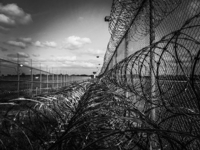 A barbed wire prison fence in black and white.