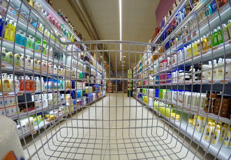 A trolley being pushed in the toiletry aisle of a supermarket.