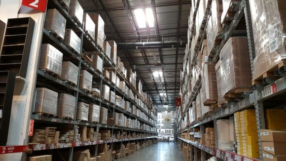 Industrial Warehouse Interior with ceiling-high shelves full of cardboard boxes.
