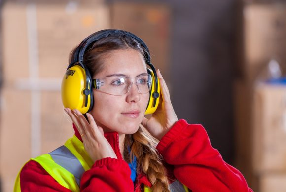 A women wearing a red jacket with a hi-vis vest on top, safety goggles and hearing protection.