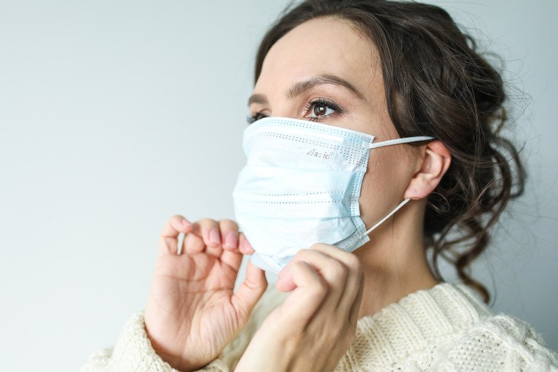 A woman wearing a surgical face mask.