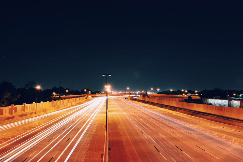 A brightly-lit motorway against the night sky.