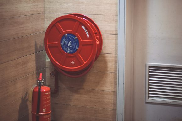 Red Fire Extinguisher Beside Hose Reel Inside a Room