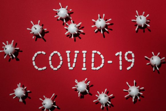 COVID-19 spelt out in small white tablets surrounded by microscopic viruses against a red background.