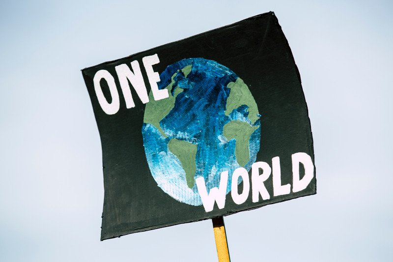 A sign with a black background then a globe and the words 'One World'.
