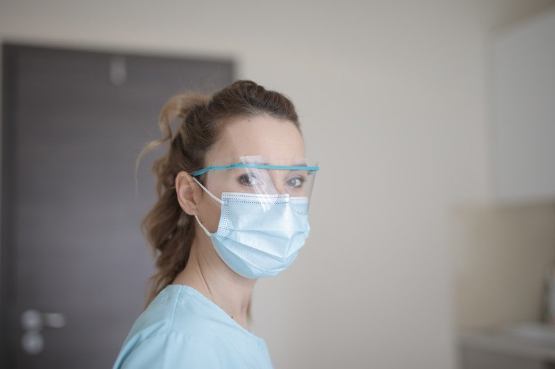 A medical worker wearing a face mask and protective eyewear..