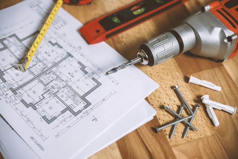 A floor plan on on a table with a tape measure, level, drill and screws.