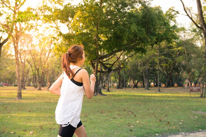 A woman in black and white activewear running through a park on a sunny day.