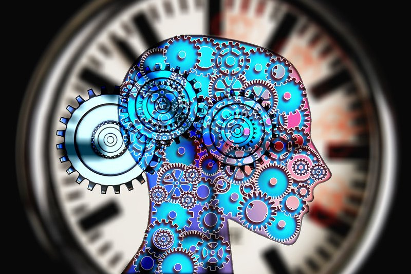 A human head with blue and pink cogs inside against a clock.