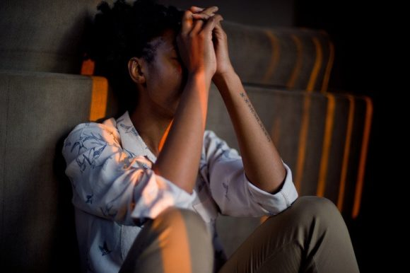 A woman showing signs of anxiety and stress by sitting with her hands covering her face.