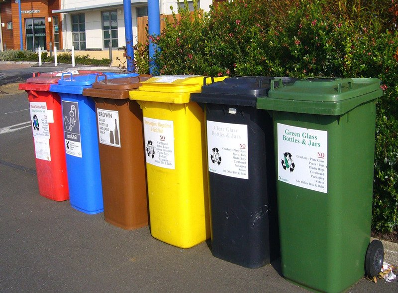 A row of multiple colours of recycling bins.
