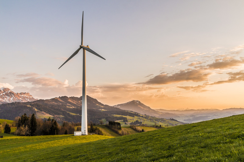 A wind turbine in a field surrounded by cliffs and trees.