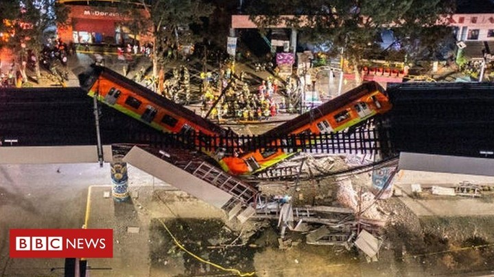 Two train carriages hanging from a collapsed metro overpass in Mexico City