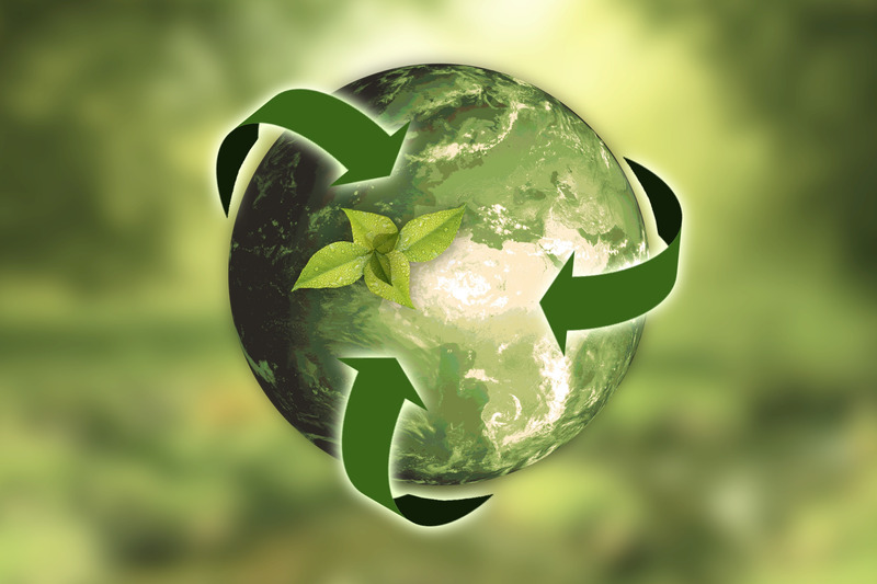 A green Earth with recycling arrows around it and a plant growing on top of it.
