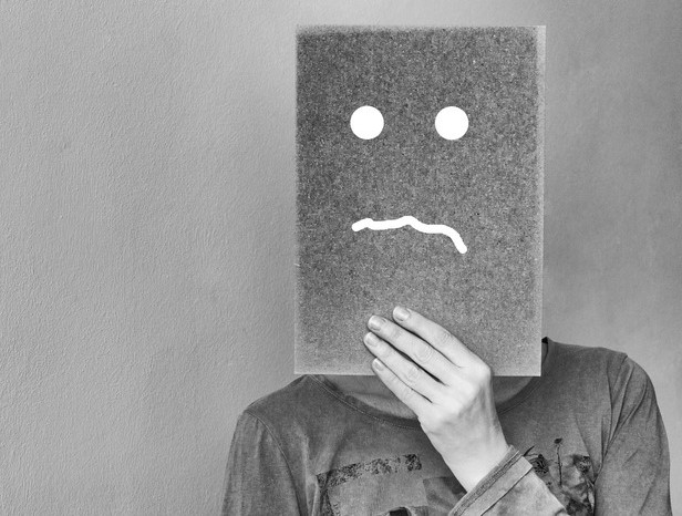 A black of white picture of a person covering their face with a sheet with a sad face drawn on it.
