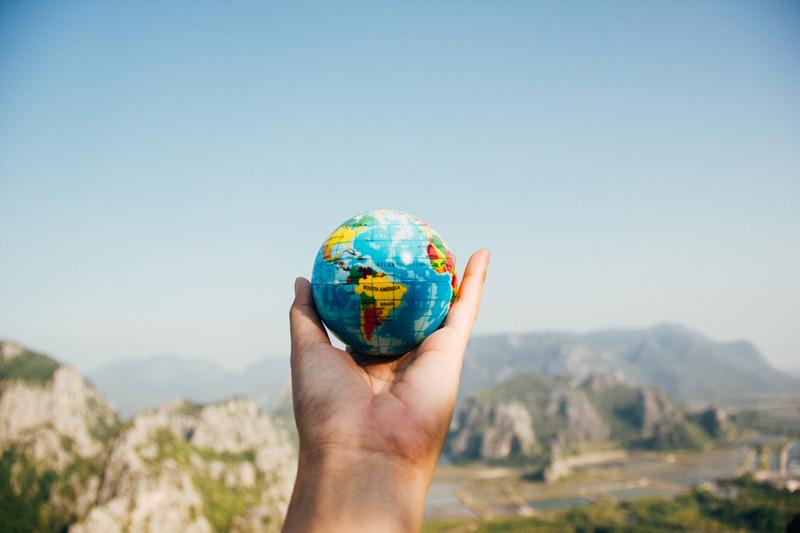A an outreached hand holding a miniature globe facing a mountain.